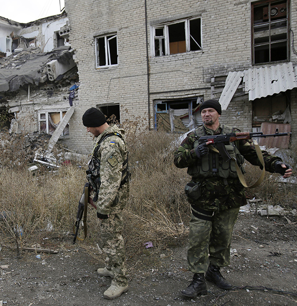 Ukrainian servicemen walk in the yard of a destroyed building in the Pisky village near Donetsk on October 26, 2015.