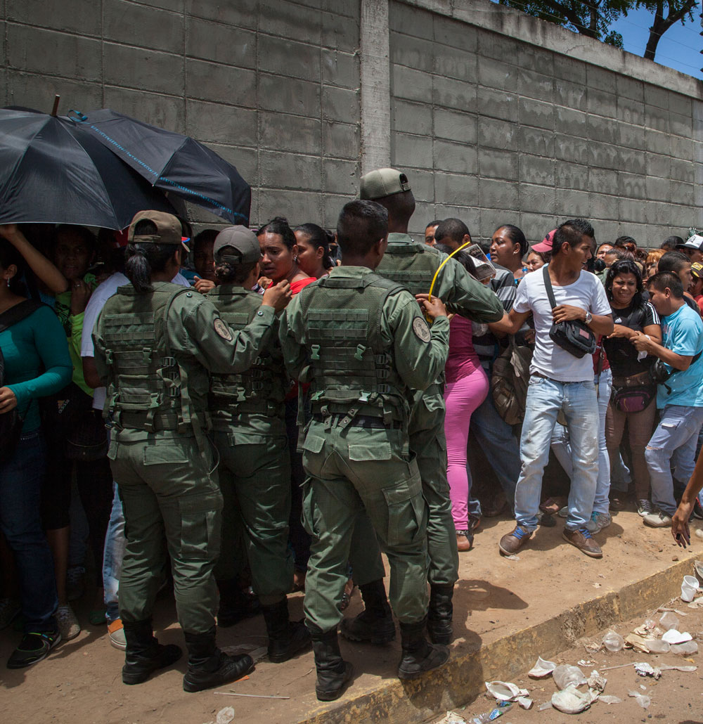 Soldiers maintain order as people form a line to buy groceries in Puerto Ordaz, Venezuela, August 6, 2015.
