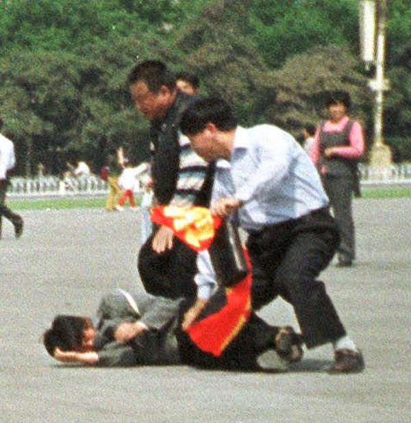 Chinese police struggle to remove a banner from a Falun Gong protester in Tianamen Square,  May 13, 2000.  (AP Photo/Chien-min Chung)