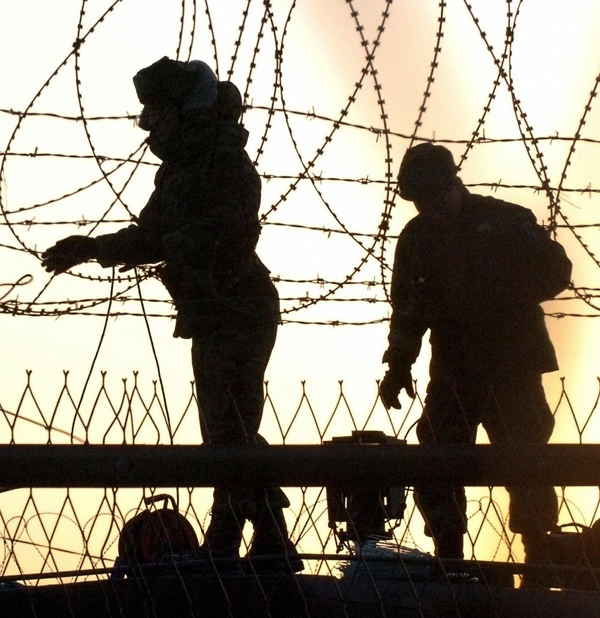South Korean soldiers check barbed wire fence along the border in Paju, near the Demilitarized Zone the two Koreas, February 10, 2005.  (Jung Je/AFP/Getty Images)