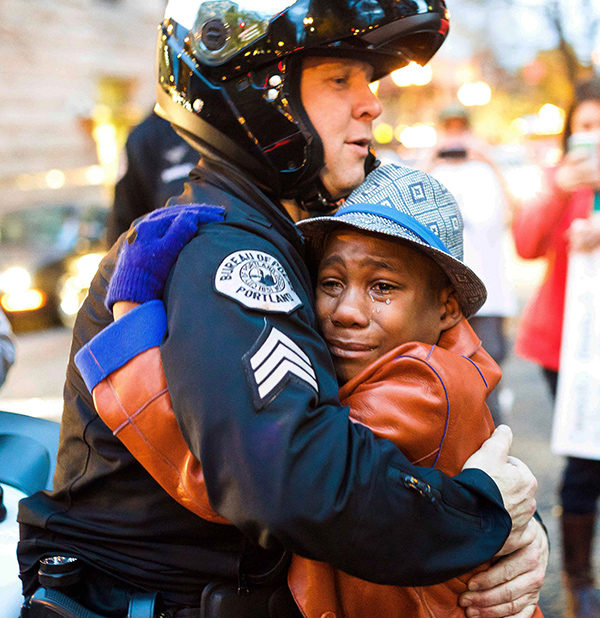 "This photo of Portland Police Sgt. Bret Barnum hugging Devonte Hart at a Ferguson demonstration in Portland, Oregon went viral and was nicknamed ""the hug shared around the world."""