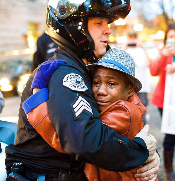 """This photo of Portland Police Sgt. Bret Barnum hugging Devonte Hart at a Ferguson demonstration in Portland, Oregon went viral and was nicknamed """"the hug shared around the world."""""""