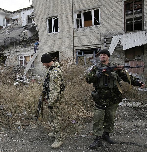 Ukrainian servicemen walk in the yard of a destroyed building in the Pisky village near Donetsk on October 26, 2015.