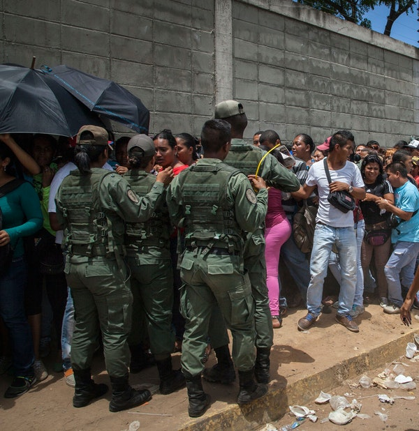 Soldiers maintain order as people form a line to buy groceries in Puerto Ordaz, Venezuela, August 6, 2015.