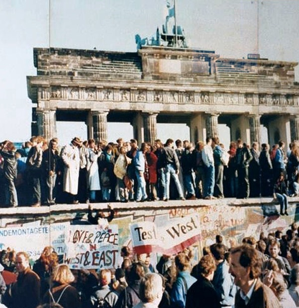 Germans storm the Berlin Wall before its destruction, 1989.