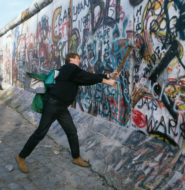 A man wields a pickaxe to participate in the destruction of the Berlin Wall, November 10, 1989. (Jacques Langevin/Sygma/Sygma via Getty Images)