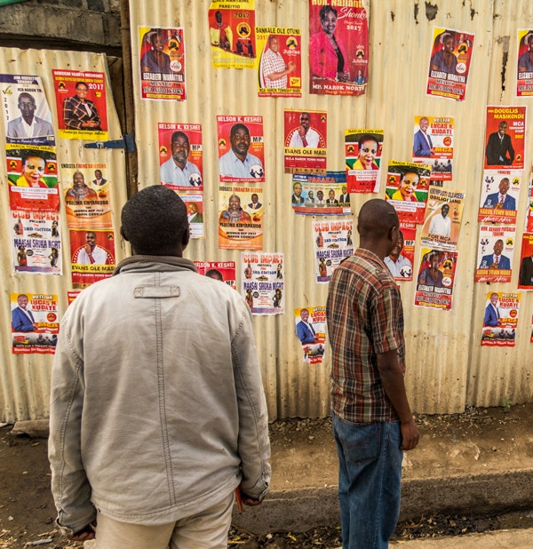 People walking past a wall of election campaign posters in Narok County, Kenya in the run-up to the national elections in August 2017.  (Stephen Butler / Shutterstock)