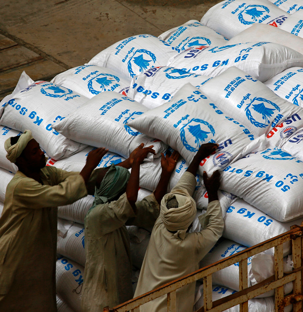 Sudanese workers offload US aid destined for South Sudan from the World Food Programme (WFP) at Port Sudan on March 19, 2017. (Ashraf Shazly/Getty Images)