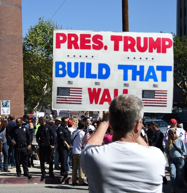 A counter-protester holds a sign reading 'Pres. Trump Build That Wall.'  (Robyn Beck/AFP/Getty Images)