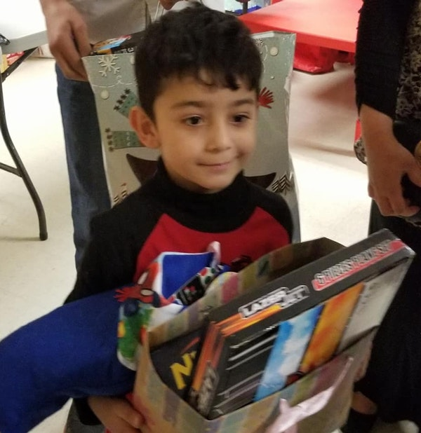 A refugee child holds his Christmas gifts at an event by Gateway of Grace, a Dallas-based non-profit organization. (via Facebook)